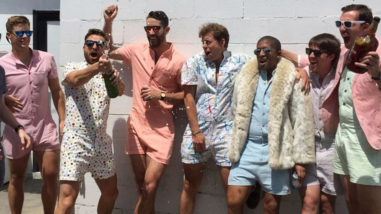 seven male models in ridiculous one piece baby suits known as rompers