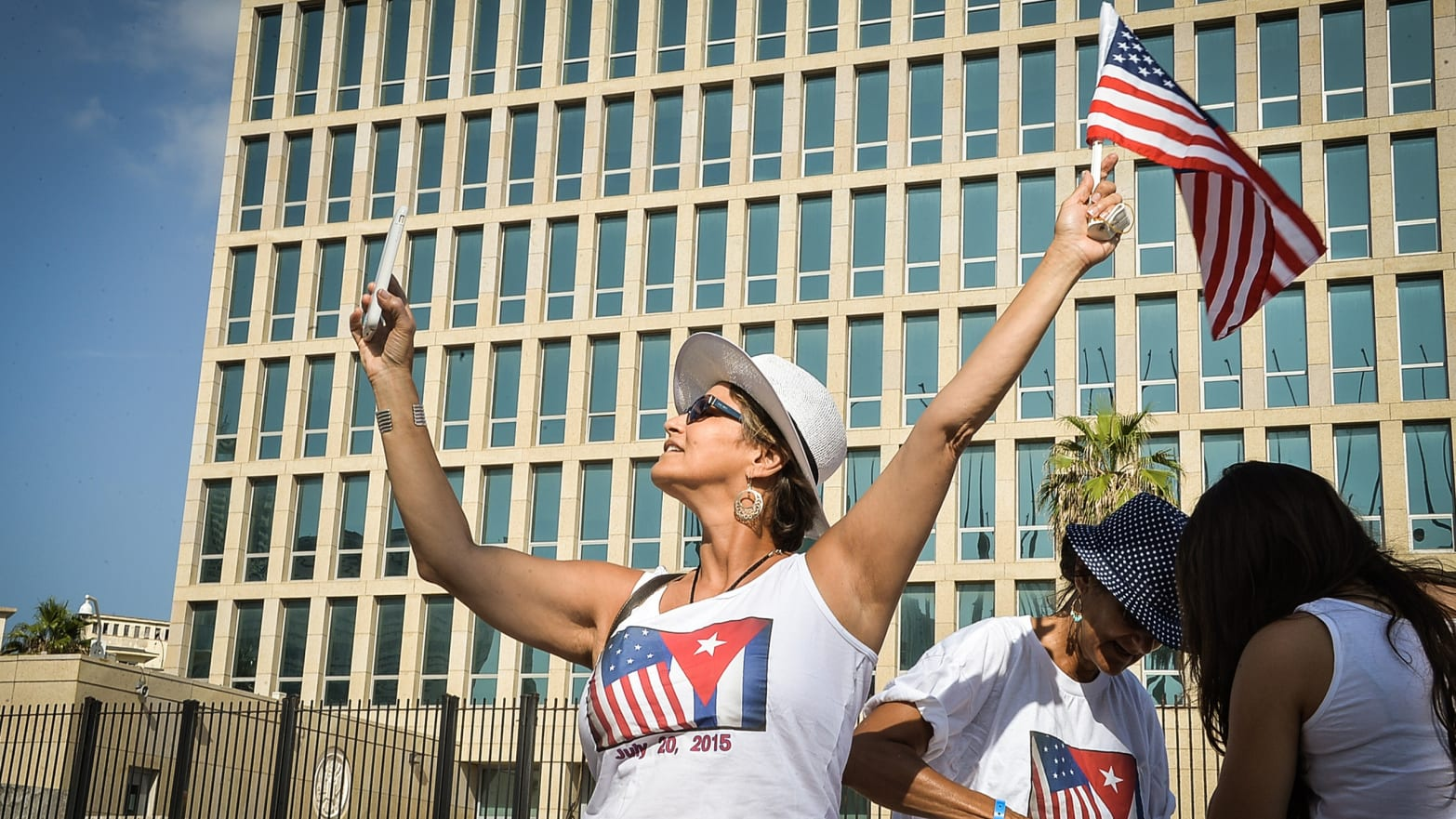 A tourist makes a selfie holding a US Flag in front of the US Embassy in Havana