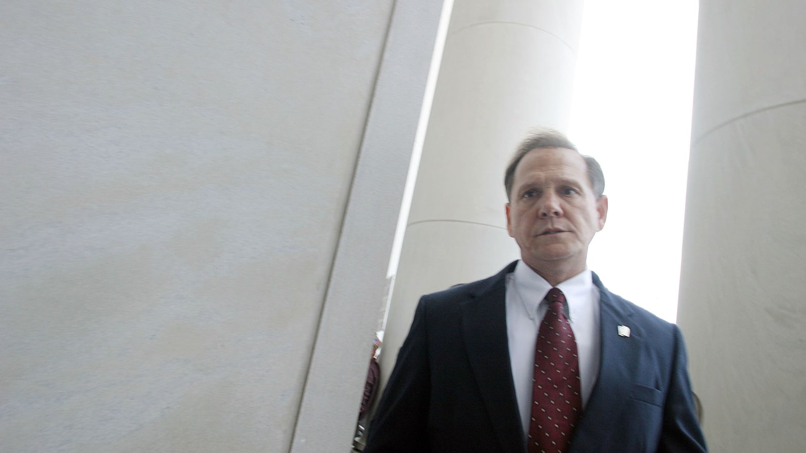 Alabama Supreme Court Chief Justice Roy Moore walks back into the state Judicial Building after addressing supporters.
