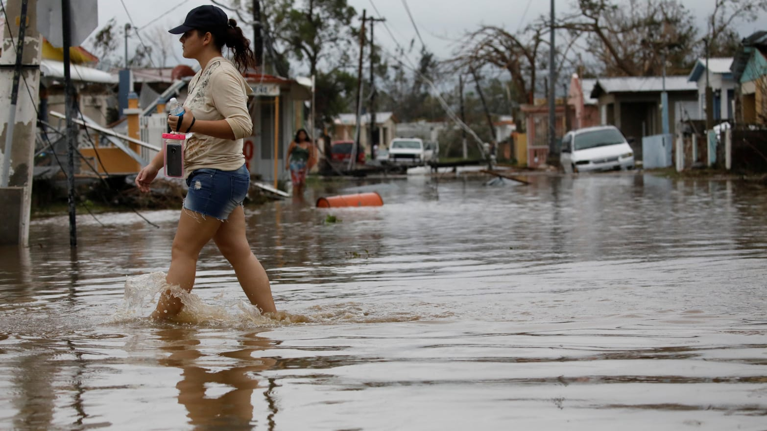 A woman wades through a flooded street after the area was hit by Hurricane Maria in Salinas, Puerto Rico, September 21, 2017.