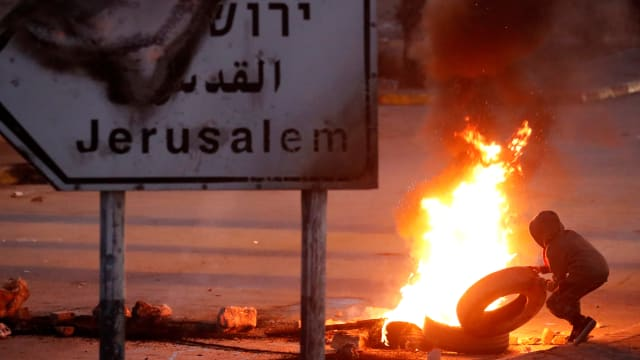 A Palestinian protester sets up a burning barricade near the West Bank city of Ramallah December 8, 2017.