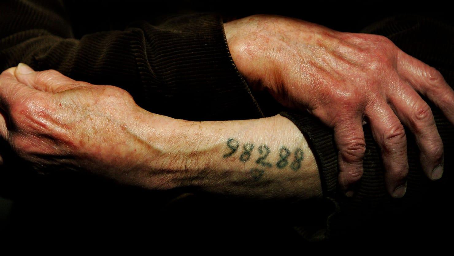 Auschwitz survivor Mr. Leon Greenman, prison number 98288, displays his number tattoo.