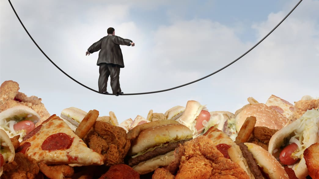 image of overweight man in a suit walking a tightrope over fast food like pizza onion rings chicken nuggets fried hamburgers obesity obese cancer gallbladder baby boomer