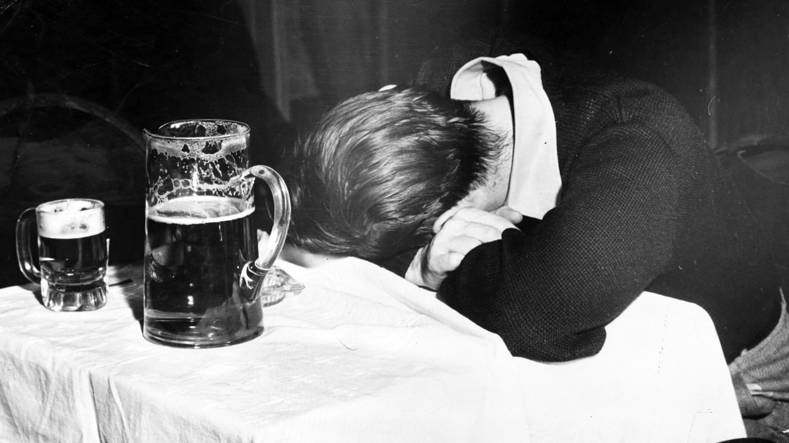 A man sleeps with his head on a table beside a pitcher of beer and a half-empty glass in a New York City bar.