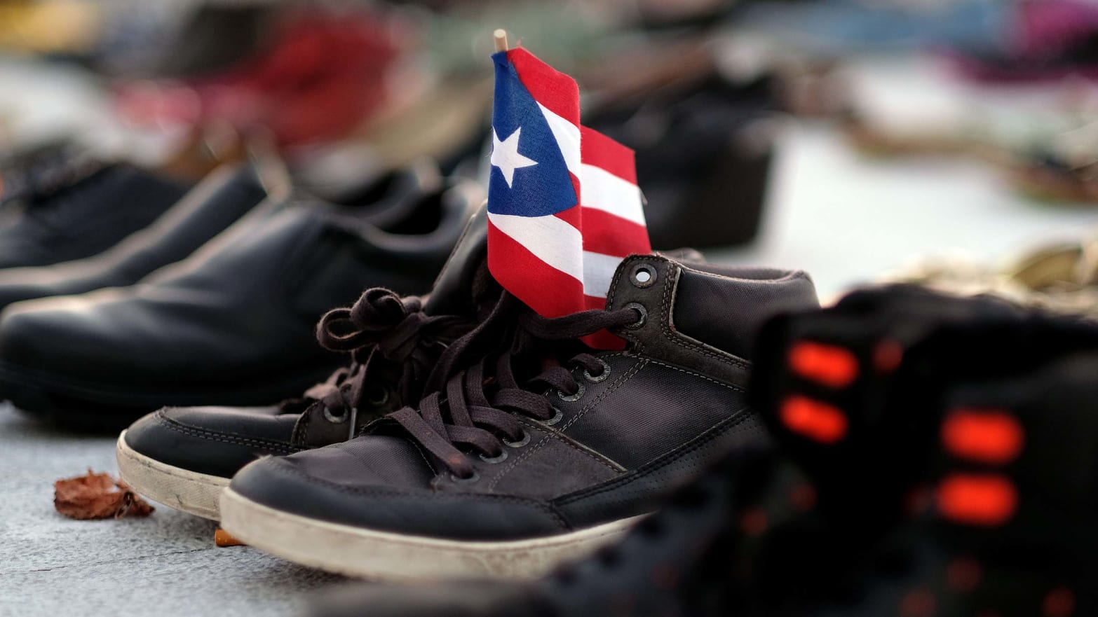 shoes holding puerto rico flag death toll maria katrina counting death statistic demography george washington harvard university climate change global warming