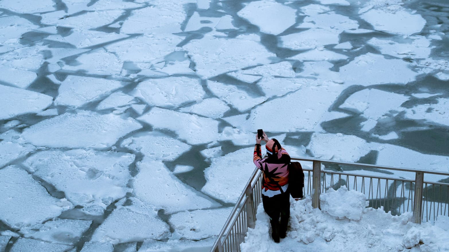 pedestrian stopping by chicago river to take picture of ice polar vortex frost quake frostquake steven battaglia climate change