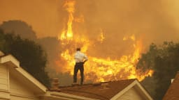 man watching fire flames on his roof carbon emissions global warming ipcc climate change 2 degrees co2 carbon dioxide carbon emissions negative becss bioenergy with carbon capture storage