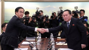 Head of the North Korean delegation, Ri Son Gwon shakes hands with South Korean counterpart Cho Myoung-gyon as they exchange documents after their meeting at the truce village of Panmunjom in the demilitarised zone separating the two Koreas, South Korea, January 9, 2018.