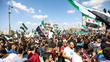 Syrians from the rebel-held northern city of Idlib and its surrounding towns wave the flag of the opposition and chant slogans as they gather for an anti-government demonstration in a main square in Idlib on September 14, 2018. (Photo by OMAR HAJ KADOUR / AFP)        (Photo credit should read OMAR HAJ KADOUR/AFP/Getty Images)