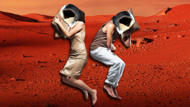 image of two people sleeping in silk pajamas with astronaut head gear with mars in the background red planet hibernation torpor passengers jennifer lawrence chris pratt sleep pod