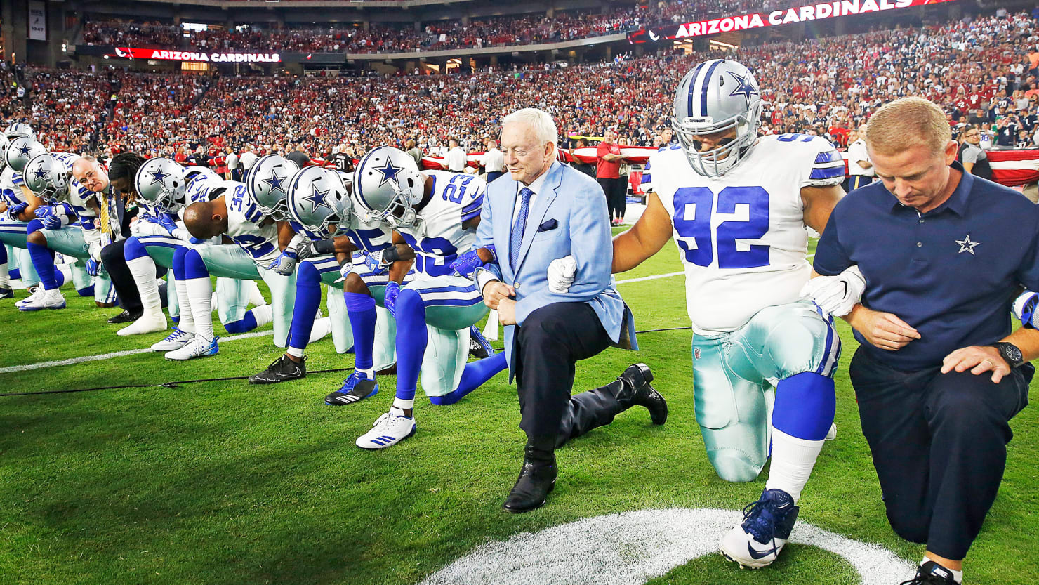 Dallas Cowboys owner Jerry Jones and head coach Jason Garrett kneel with their team