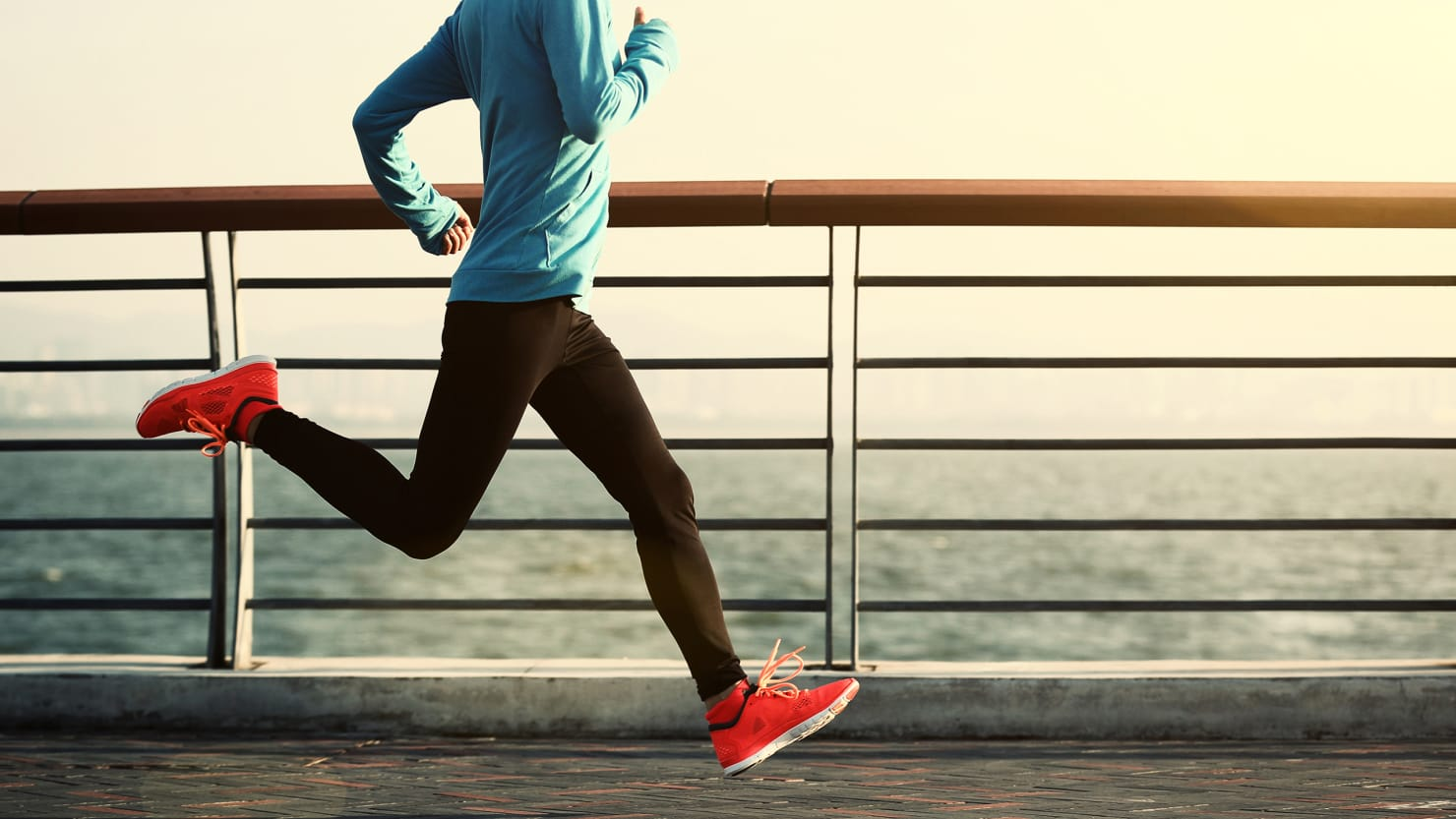 image of runner wearing turquoise top and black leggings with ocean behind spf uva uvb sunscreen skin cancer upf ultra protection factor clothing