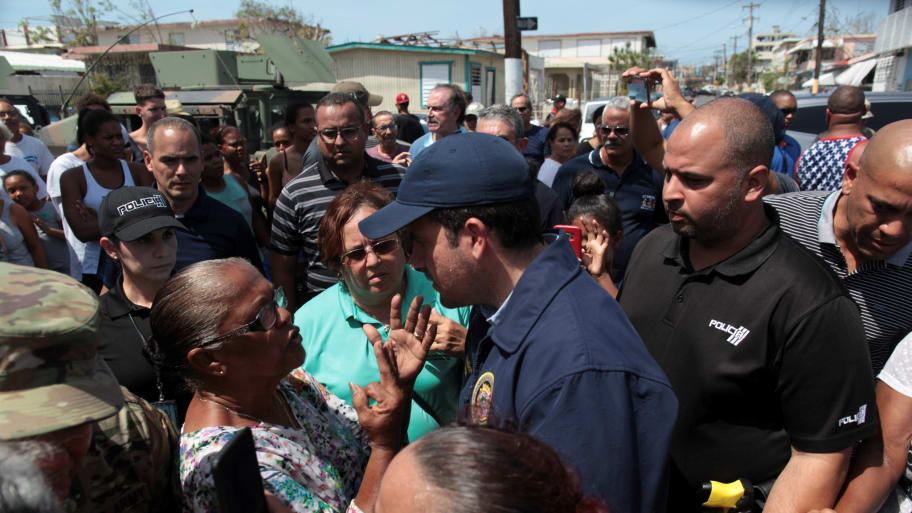 Puerto Rico's Governor Ricardo Rossello talks to a woman during a distribution of relief item
