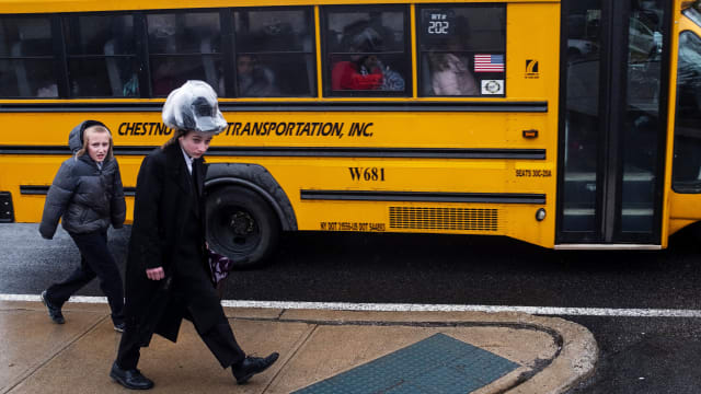 photo of two boys walking next to a school bus in a jewish neighborhood in monsey rockland county new york measles outbreak anti vax antivax rockland country de blasio forced vaccination del bigtree lawrence palevsky andrew wakefield williamsburg orthodox