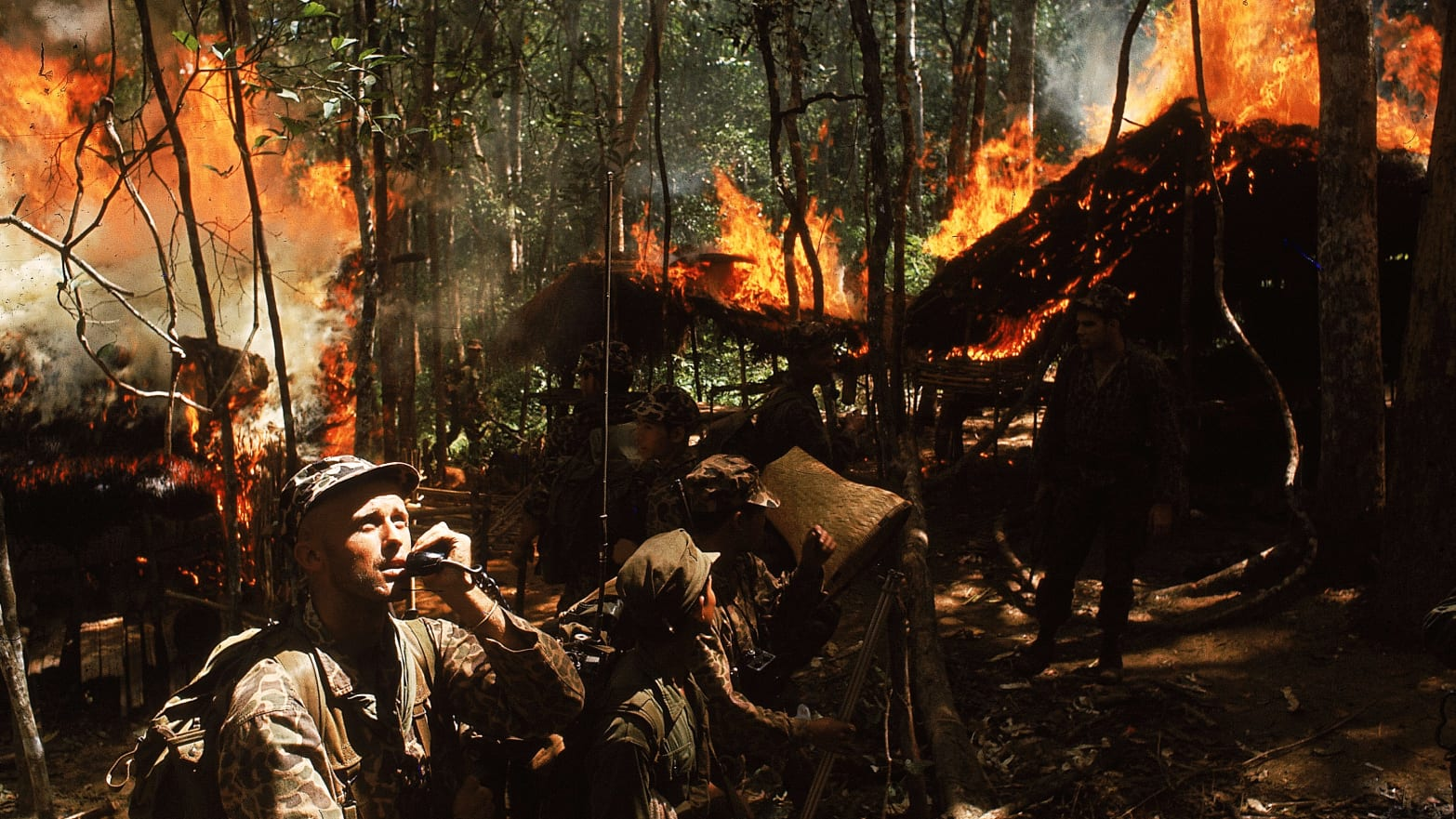 U.S. Army Special Forces Capt. Vernon Gillespie contacting his base camp by radio while Vietnamese soldiers burn down a National Liberation Front hideout.