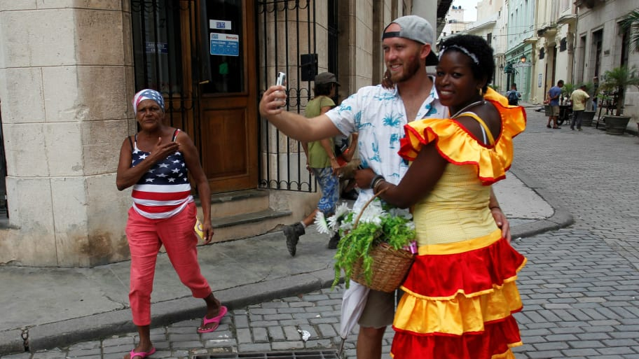 An American tourist (2nd R) takes a selfie in Havana, Cuba, September 29, 2017.