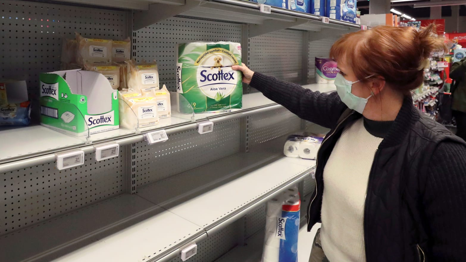 A woman wearing a protective face mask looks for toilet paper in a supermarket.