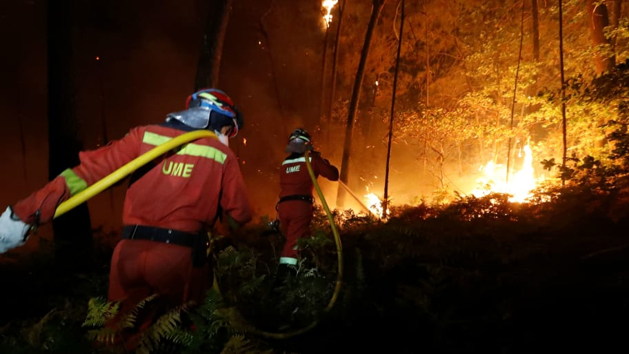 Firefighters from the Military Emergency Unit (UME) work to put out a forest fire near As Nieves, northern Spain, October 15, 2017.