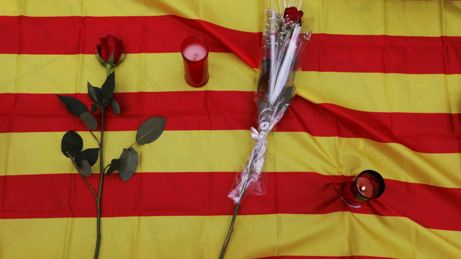 Roses and candles placed on Catalan flag at impromptu memorial service for Barcelona attack victims.