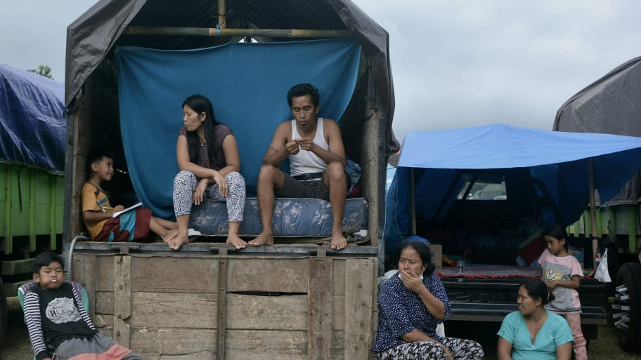 Villagers who live near Mount Agung sit inside a truck as a temporary tent near a sport arena in Klungkung.