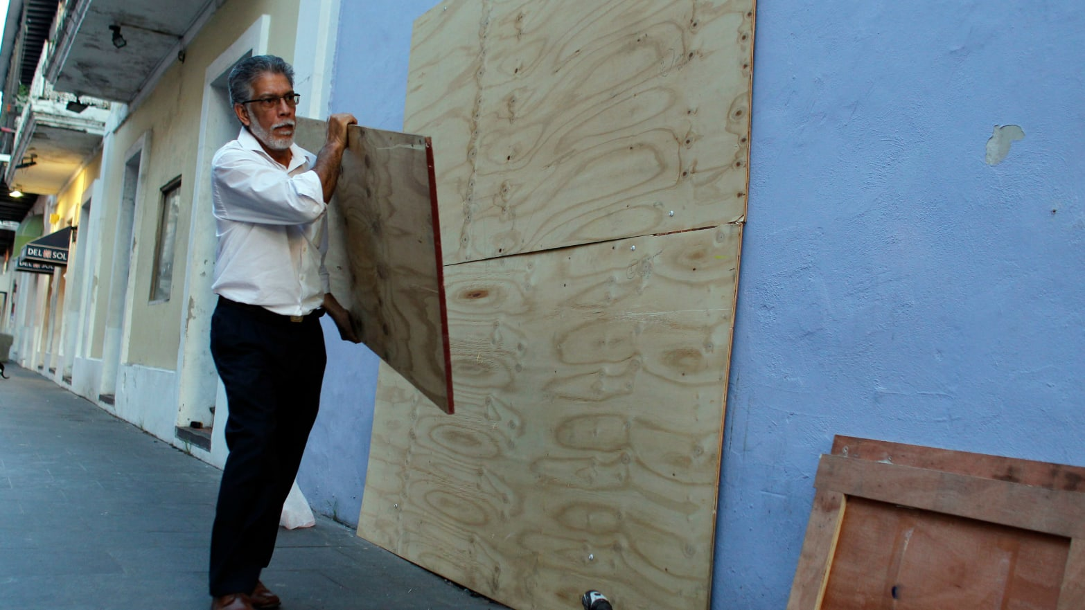 A man boards up windows of a business in preparation for Hurricane Maria in San Juan, Puerto Rico