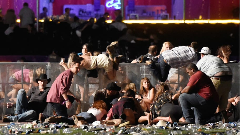 People scramble for shelter at the Route 91 Harvest country music festival after apparent gun fire was heard on October 1, 2017 in Las Vegas, Nevada. A gunman has opened fire on a music festival in Las Vegas