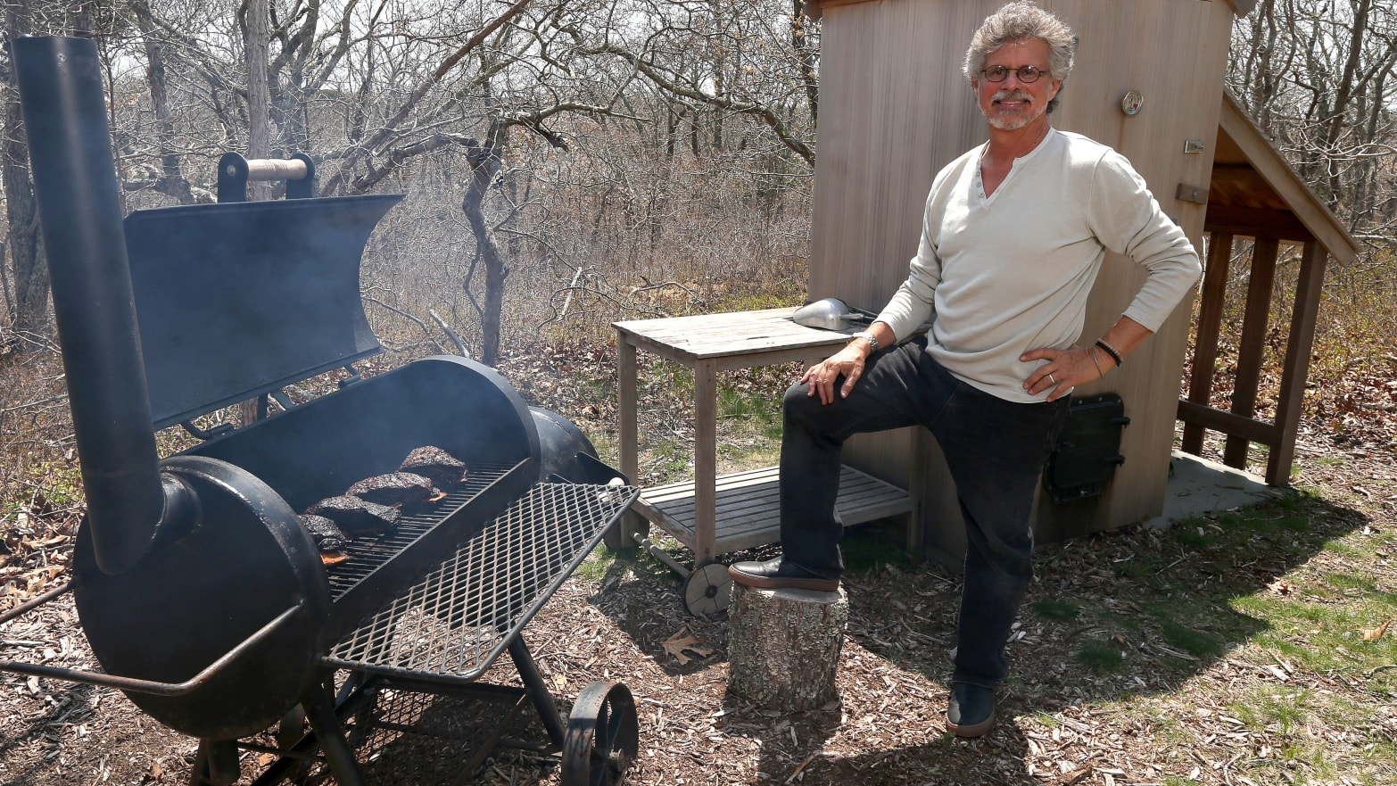 Steven Raichlen poses while cooking Oak smoked big bad beef ribs
