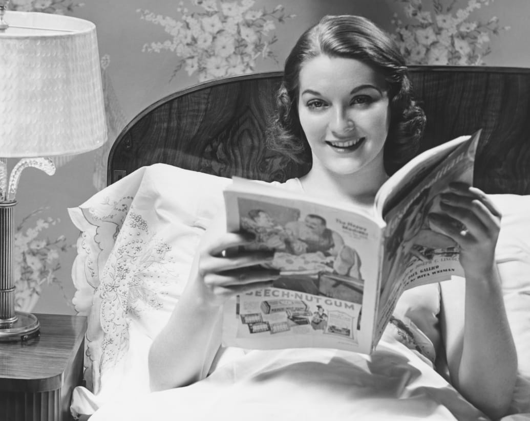 50s woman in bed, reading magazine