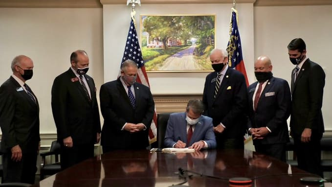 """Jim Crow 2.0.""? Photo of Georgia Gov. Brian Kemp Signing Voter Suppression Bill Into Law Under Painting of Slave Plantation While Surrounded By White Republican Men Goes Viral"