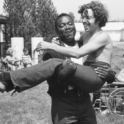 Homem negro com deficiência carrega homem branco com deficiência