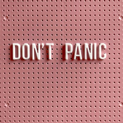 "Pink pegboard sign with ""Don't Panic"" written in lighter pink stick-on letters"